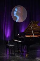 Fortepian na scenie, artyści stoją na scenie w eleganckich ubraniach i śpiewają. Publiczność siedzi na widowni. Artyści cieszą się z werdyktów.