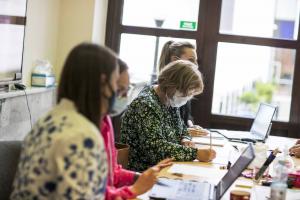 Cztery kobiety w maseczkach siedzą przy stole.
