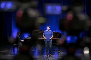 Mężczyzna w niebieskiej koszulce śpiewa na scenie, a obok niego kobieta gra na fortepianie.
