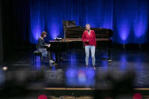 Kobieta w czerwonym swetrze śpiewa na scenie, a obok niej kobieta gra na fortepianie.