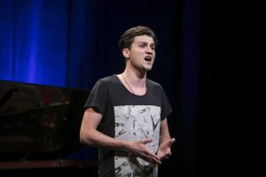 Mężczyzna w koszulce śpiewa.