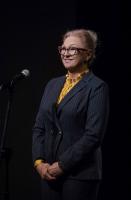 Uśmiechnięta kobieta stoi przy mikrofonie.