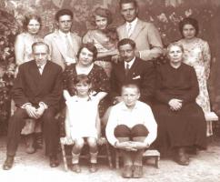 Grupa ludzi siedzi i pozuje do zdjęcia.