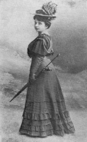 Kobieta w długiej sukni, w kapeluszu stoi tyłem, a w ręku trzyma laskę.