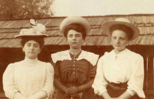 Trzy kobiety w kapeluszach stoją obok siebie.