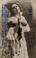 Kobieta w długiej sukni stoi z ręku podniesioną na wysokość ramion.