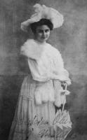 Kobieta w w długiej, ozdobnej sukni i w kapeluszu stoi.
