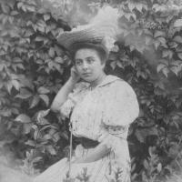 Kobieta w sukni i w kapeluszu siedzi.