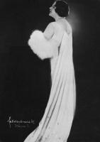 Kobieta w ozdobnej sukni stoi.