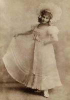 Kobieta w długiej sukni stoi. Jedną ręką podtrzymuje bok sukni.