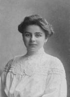Kobieta w białej sukni pozuje do zdjęcia.