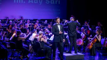 mężczyzna śpiewa na scenie, w tle widać orkiestrę