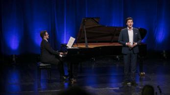 młody mężczyzna stoi na scenie, lekko za nim znajduje się fortepian, na którym gra drugi mężczyzna