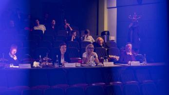 ciemna sala, ludzie siedzący na widowni