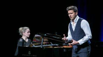 elegancko ubrany mężczyzna śpiewa na scenie, za nim widać fortepian i grającą na nim kobietę