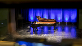 fortepian stojący na scenie, podświetlony niebieskim światłem