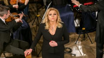 kobieta w czarnej sukni stoi między muzykami orkiestry