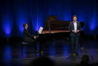 Młody mężczyzna w garniturze, stoi na scenie. Za nim widać fortepian, na którym gra drugi mężczyzna.