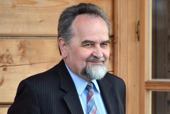 popiersie uśmiechajacego się mężczyzny w garniturze i krawacie