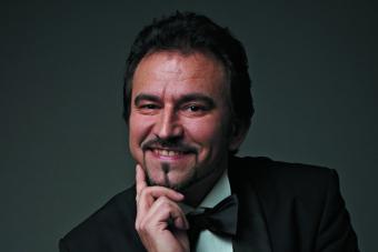 mężczyzna w eleganckim stroju, prawdopodonie fraku, koszuli i z muszka pod szyją, podpiera głowę, uśmiecha się