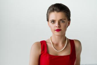 kobieta w czerwonej sukni z perłami na szyi