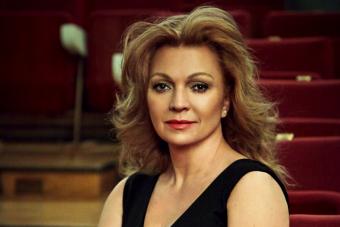 kobieta w sukni siedzi w sali koncertowej na widowni, włosy rozpuszczone swobodnie opadają na ramiona, patrzy na wprost
