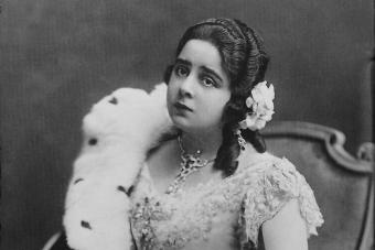 Kobieta z zarzuconym na ramię futrem siedzi na ozdobnym fotelu