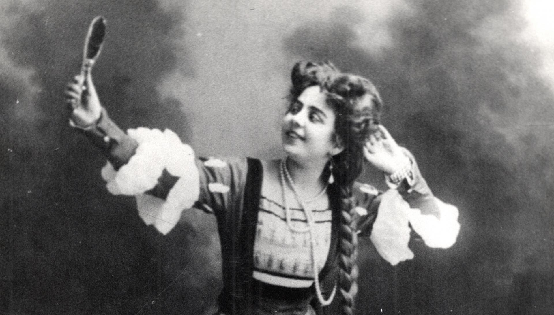 kobieta z długim warkoczem przegląda się w trzymanym w ręku lusterku